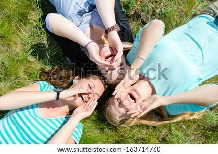 Two happy teen girls lying on green grass and holding hands in summer outdoors