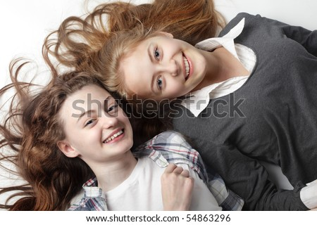 two happy teen laying on floor - stock photo