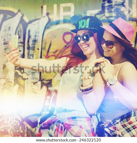 Two happy teenage girlfriends taking a selfie with smartphone outdoors on sunny summer day against graffiti wall. Square format, filter, saturated colors, light leak effect. - stock photo