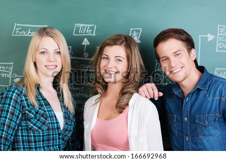 Two happy teenage girls and a boy in class posing together in front of the chalkboard looking at the camera with warm friendly smiles - stock photo