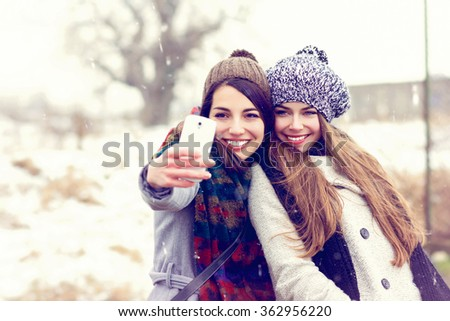 Two happy teenage girls in coats, knitted beanie hats and scarves taking a selfie on smartphone, outdoors in winter. Horizontal, retouched, filter applied. - stock photo