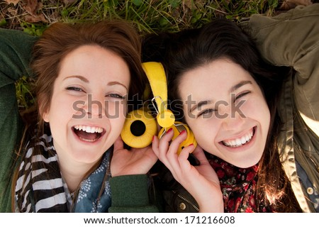 Two happy teenage girls lying on the grass sharing headphones to listen to music - stock photo