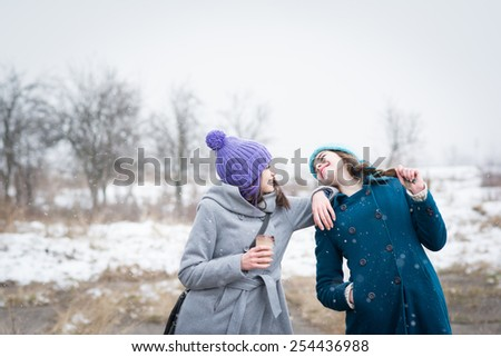 Two happy teenage girls with colorful knit beanie hats and colorful hair enjoying winter and snow outdoors. Young women in park with takeaway coffee laughing having fun on cold day. Mildly retouched. - stock photo
