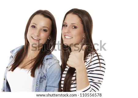 two happy teenager showing thumbs up on white background - stock photo