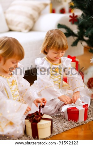 Two happy twins girl opening presents near Christmas tree