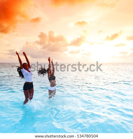 Two happy wimen playing in water on sunset