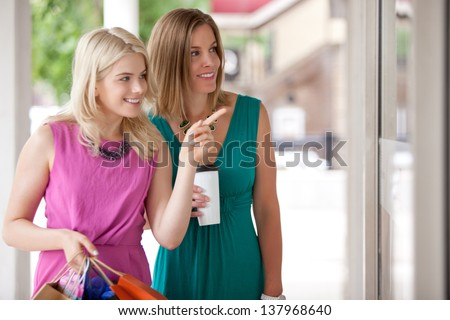 Two happy window shopping women looking at merchandise - shallow depth of field, critical focus on woman in green