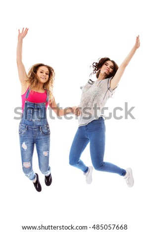 Two happy woman jumping together