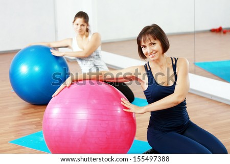 two happy women at the gym with a pilates ball