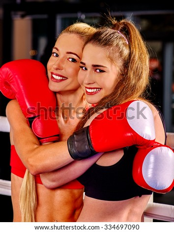 Two happy women boxer wearing red  gloves posing in ring. - stock photo