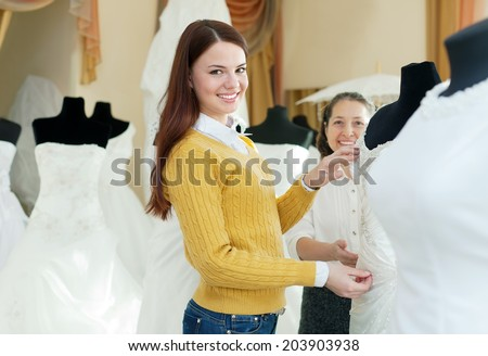 Two happy women chooses bridal outfit at  wedding boutique. Focus on bride - stock photo
