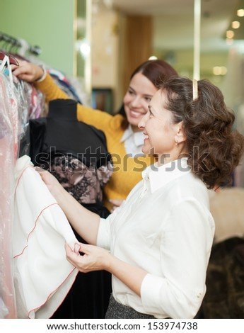 Two happy women chooses evening gown at shop of fashionable clothes - stock photo