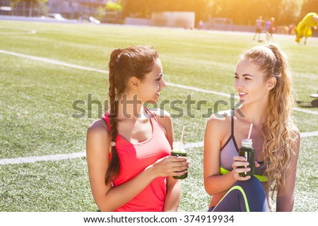 Two happy women drinking vegetable smoothie after fitness running workout on stadium. Fitness and healthy lifestyle concept