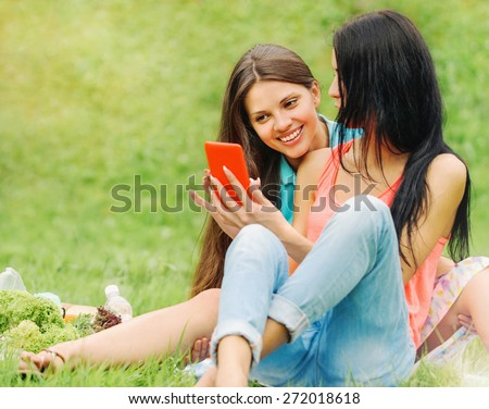 two happy women friends laughing and sharing social media pictures in a smart phone on picnic at the park, lifestyle concept - stock photo