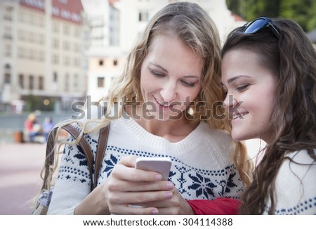 Two happy women friends sharing social media in a smart phone outdoors in a city. Two young women looking at mobile phone together while standing outdoors city. Drink coffee and discuss news - stock photo