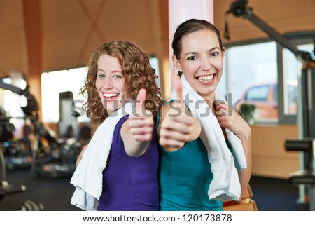 Two happy women in a fitness center holding their thumbs up - stock photo