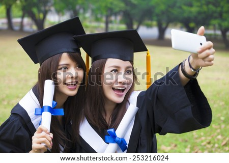 Two happy women in graduation gowns taking picture with cell phone - stock photo