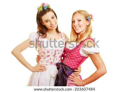 Two happy women in pink dirndl dress in Bavaria at Oktoberfest - stock photo