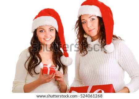 Two happy women in santa hats with gift boxes standing on white background