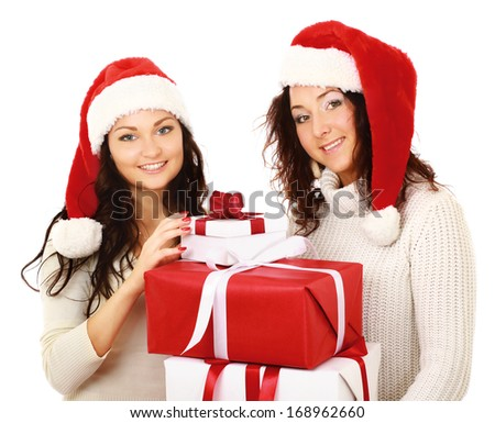 Two happy women in santa hats with gift boxes standing on white background isolated - stock photo