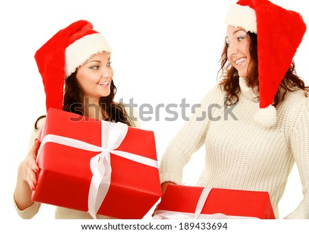Two happy women in santa hats with gift boxes standing on white background isolated. - stock photo