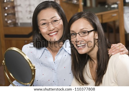 Two happy women in shop trying on spectacles