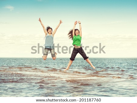 Two happy women jumping in the sea