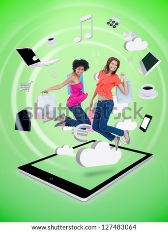 Two happy women jumping on a tablet pc against a digital green background - stock photo