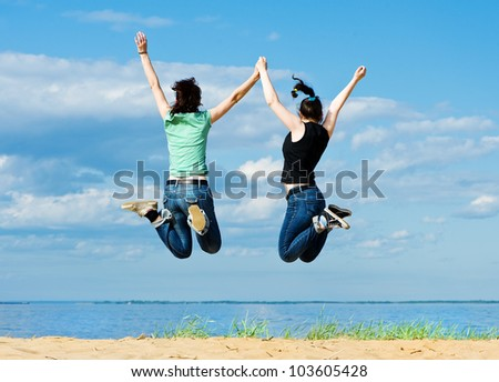 Two happy women jumping on the beach - stock photo