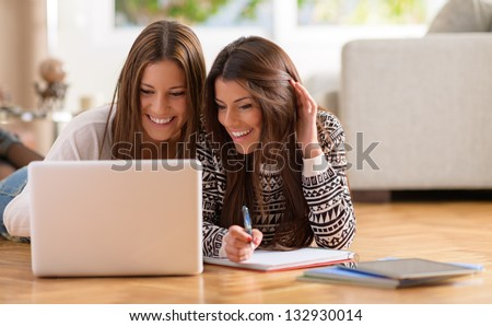Two Happy Women Looking At Laptop While Lying On Floor - stock photo