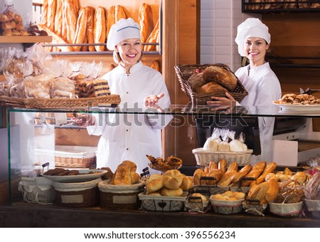 Two happy women offering bread and different pastry for sale in bakery. Focus on left woman - stock photo