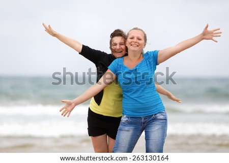 Two happy women on the beach with open arms enjoying their freedom. Shallow depth of field. - stock photo