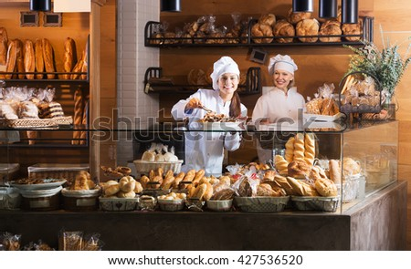 Two happy women selling bread and different pastry in bakery - stock photo