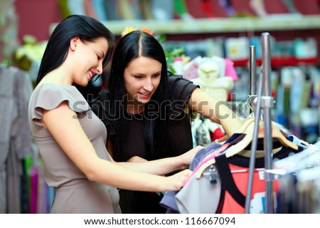 two happy women shopping in clothes store - stock photo