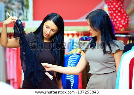 two happy women shopping in clothes store