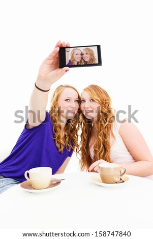 two happy women sitting at a coffee table making photos of themselves on white background - stock photo