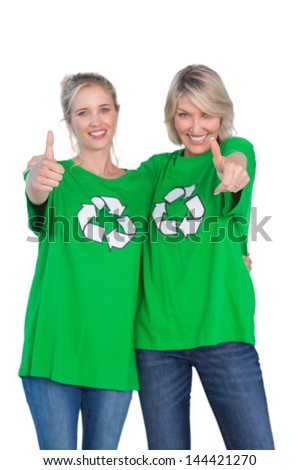 Two happy women wearing green recycling tshirts giving thumbs up on white background - stock photo