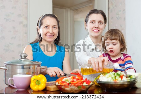 Two happy women with baby girl cook veggie lunch with vegetables and oil in kitchen at home - stock photo