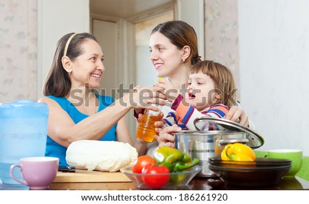 Two happy women with child cook with vegetables and oil in kitchen at home