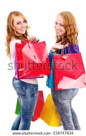 two happy women with shopping bags turning around on white background - stock photo