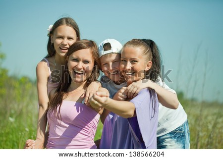 Two happy  women with teens sitting on the green grass - stock photo