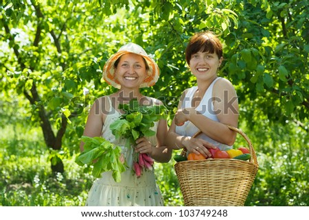 Two happy women with vegetables harvest in garden