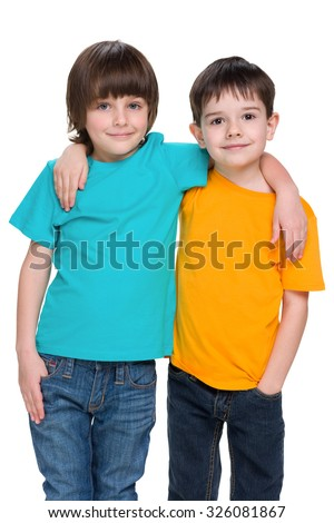 Two happy young boys are standing together against the white background