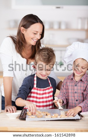 Two happy young brothers, one in a chefs toque and one in a colorful red and white apron, baking cookies in the kitchen watched over by their attractive mother - stock photo