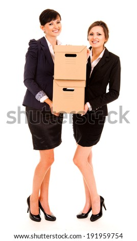 two happy young business women with carton boxes, standing and smiling, white background - stock photo