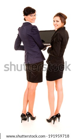 two happy young business women with laptop, standing and smiling, full lenght, white background - stock photo