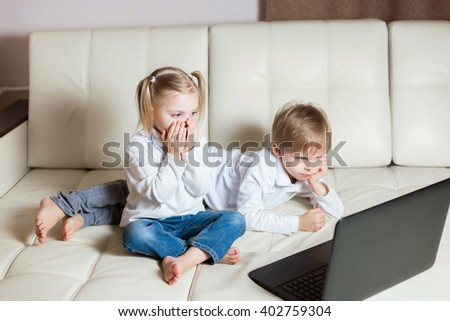 two happy young children: a blond boy lying on his stomach white-skinned girl sitting (brother and sister) on a white sofa with a laptop watching cartoons in the computer - stock photo
