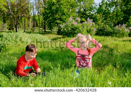 Two happy young children, a blond girl and boy, playing in lush green long grass in a garden park grinning happily at the camera as they crouch down