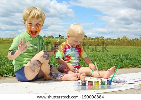 Two happy young children, a little boy and his baby brother, are sitting outside on a summer day, painting a picture, and covering themselves in paint. - stock photo
