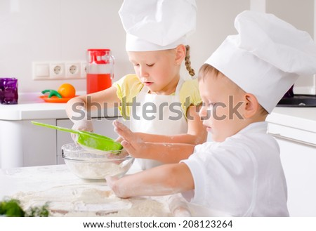 Two happy young children learning to bake with a cute little boy and girl in chefs toques and white uniforms rolling out fresh dough for biscuits - stock photo